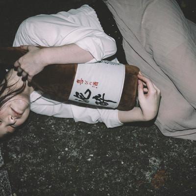 「[忘年会シーズン]泥酔して一升瓶を抱きながら路上で寝てしまった女性」の写真素材