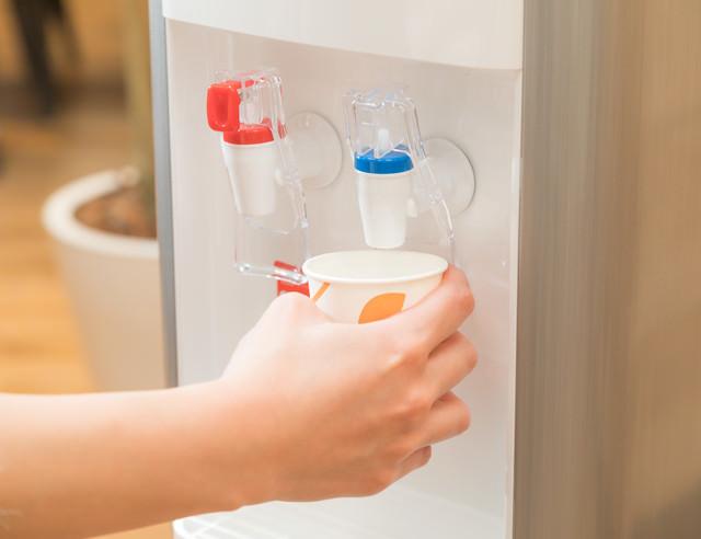 ウォーターサーバーの冷たい水を紙コップに入れるの写真