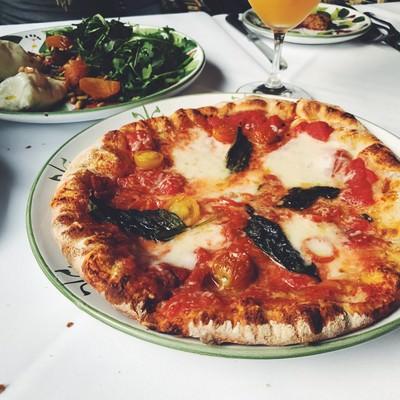 「テーブルに置かれた手作りピザ」の写真素材