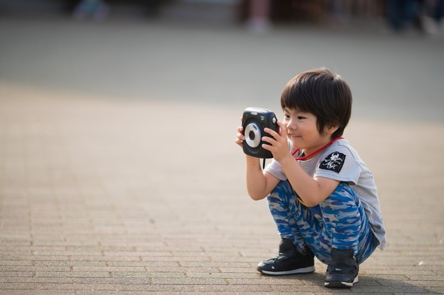 インスタントカメラに興味津々の子供の写真
