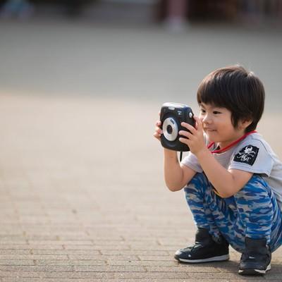「インスタントカメラに興味津々の子供」の写真素材