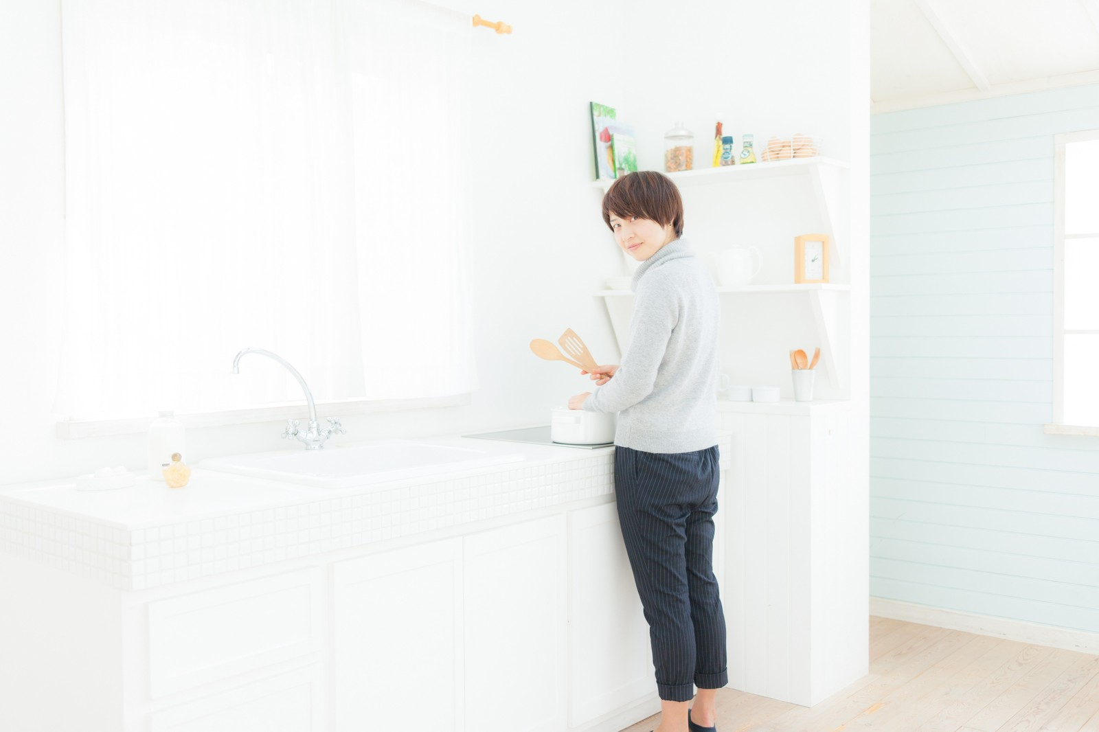 「キッチンで料理をしている若妻」の写真[モデル:八木彩香]