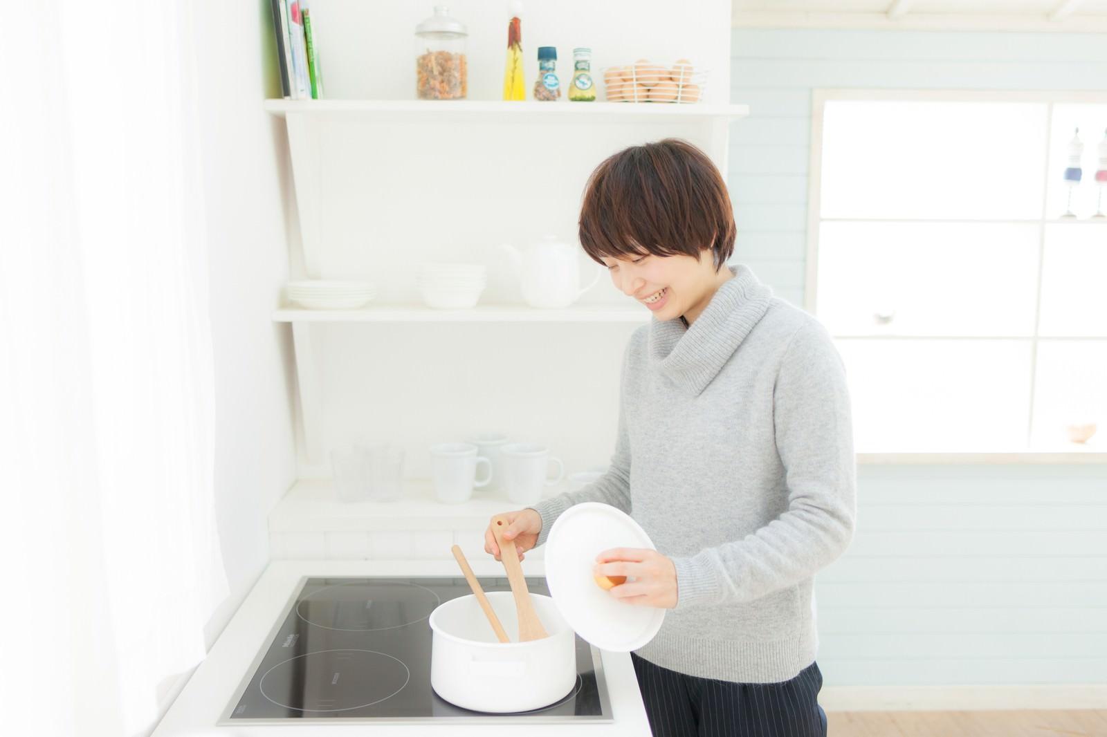「キッチンでスープを温めなおしている女性」の写真[モデル:八木彩香]