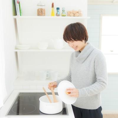 「キッチンでスープを温めなおしている女性」の写真素材