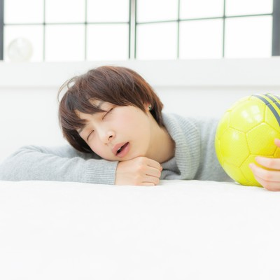 口を開けて眠るサッカーガールの写真