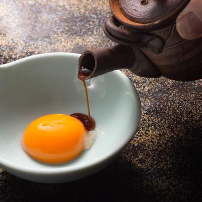 「黄身に特製醤油をかける」の写真素材