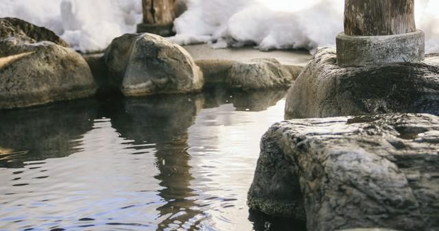 腰を掛けると滑らかで心地よい岡田旅館の岩露天風呂の写真