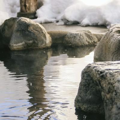 「腰を掛けると滑らかで心地よい岡田旅館の岩露天風呂」の写真素材