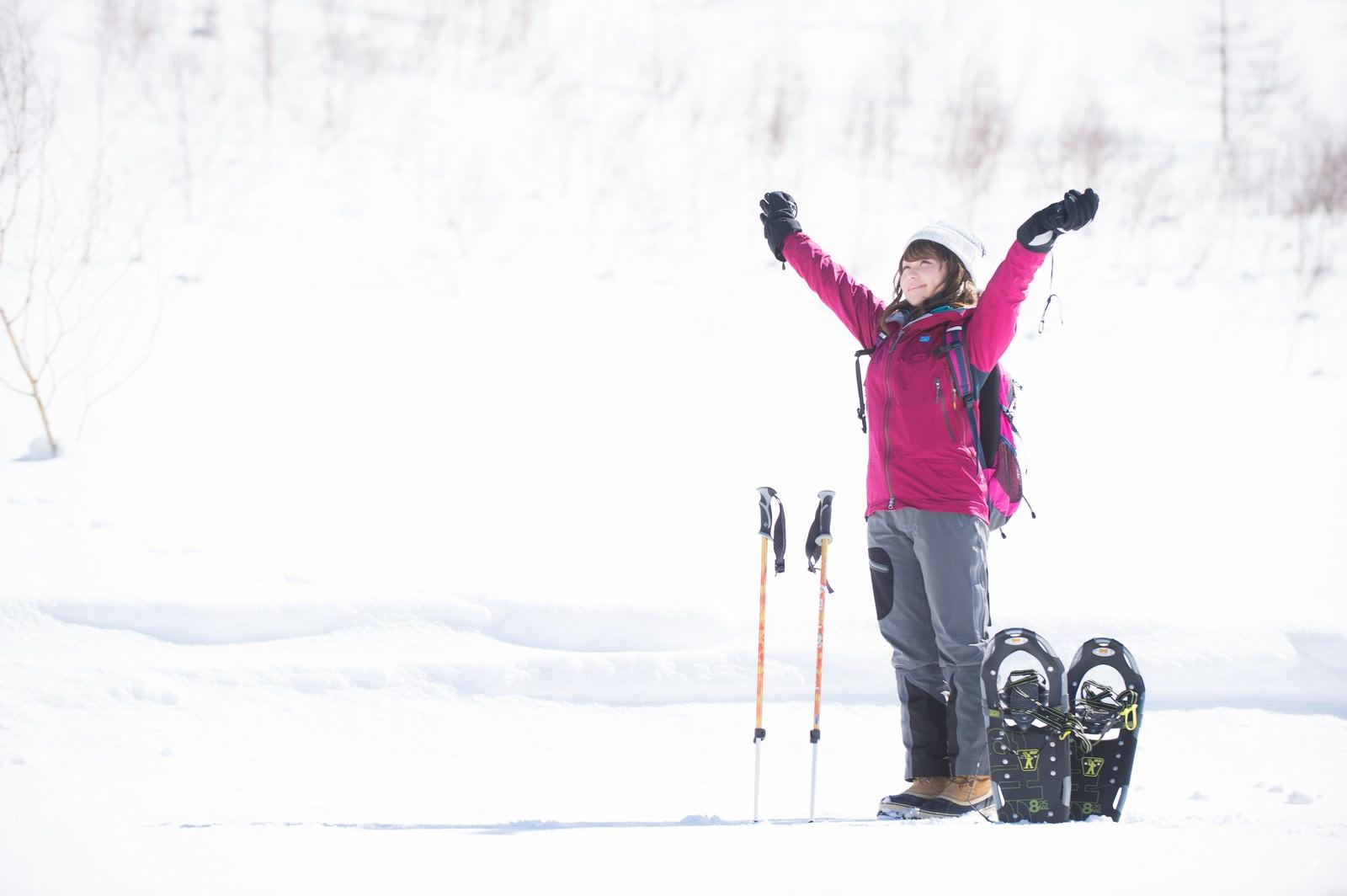 「雪山のトレッキングで大きく伸びをする女性」の写真[モデル:茜さや]