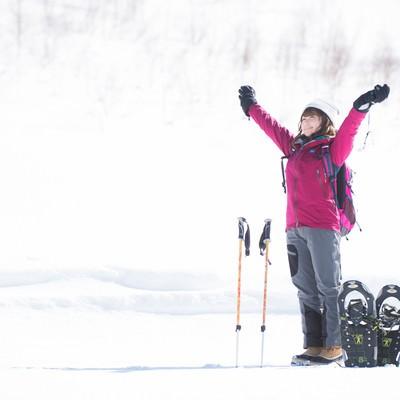 「雪山のトレッキングで大きく伸びをする女性」の写真素材