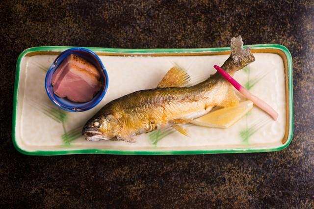 奥飛騨の渓流で釣れる魚を絶妙な塩加減で焼き上げる栄太郎の夕食の写真