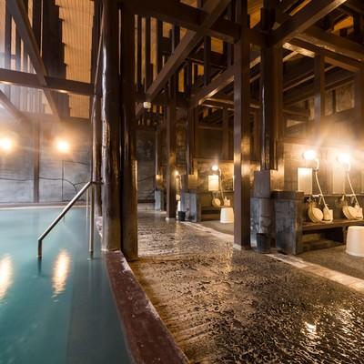 「硫黄の匂いが漂う青白く濁った源泉かけ流しの大浴場「ひらゆの森」の内湯」の写真素材