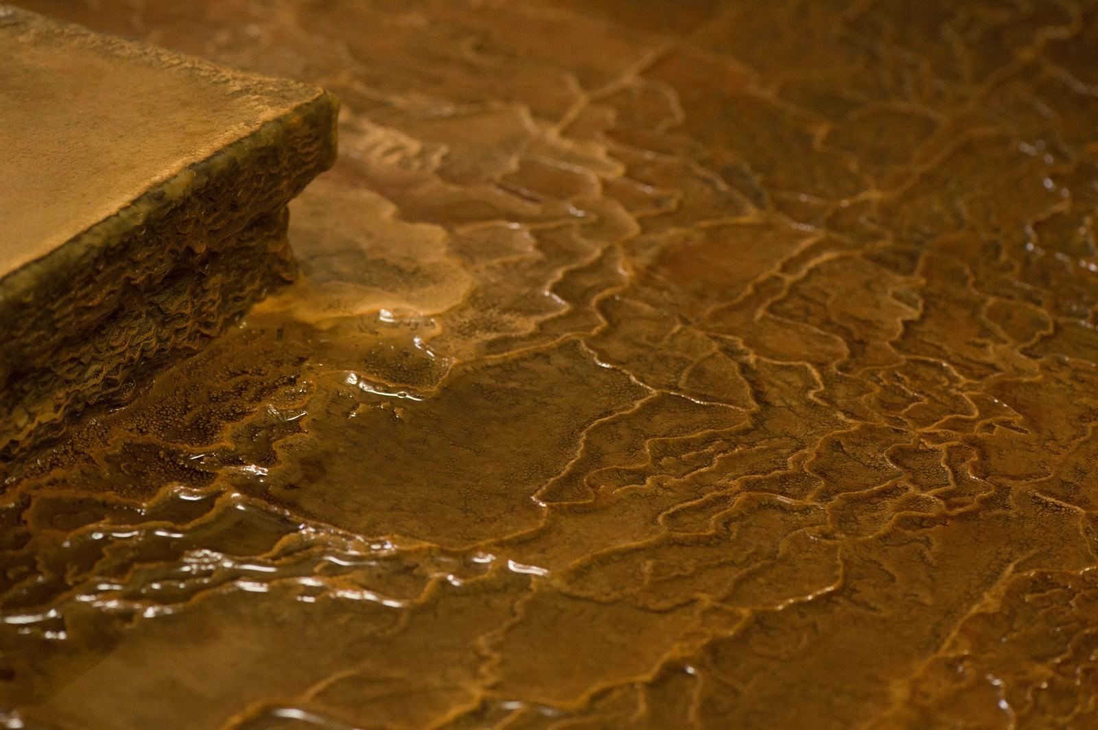 「源泉かけ流しの証である波状に溶けた「栄太郎」の浴場の床」の写真