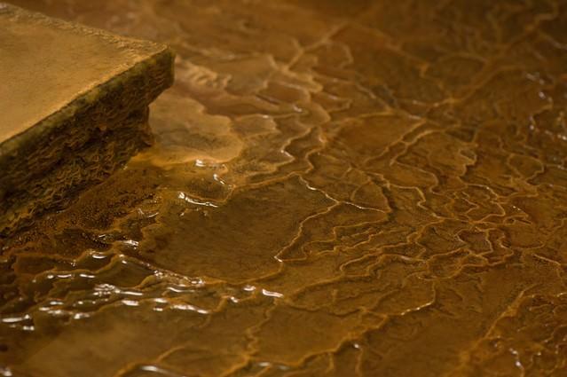 源泉かけ流しの証である波状に溶けた「栄太郎」の浴場の床の写真