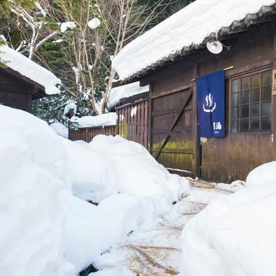 「雪の回廊の先に待つ源泉かけ流しの秘湯への期待」の写真素材