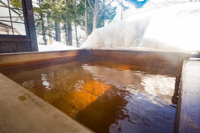 北アルプスの温泉地は雪を眺めながら源泉かけ流しの足湯の写真