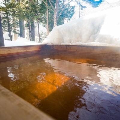 「北アルプスの温泉地は雪を眺めながら源泉かけ流しの足湯」の写真素材