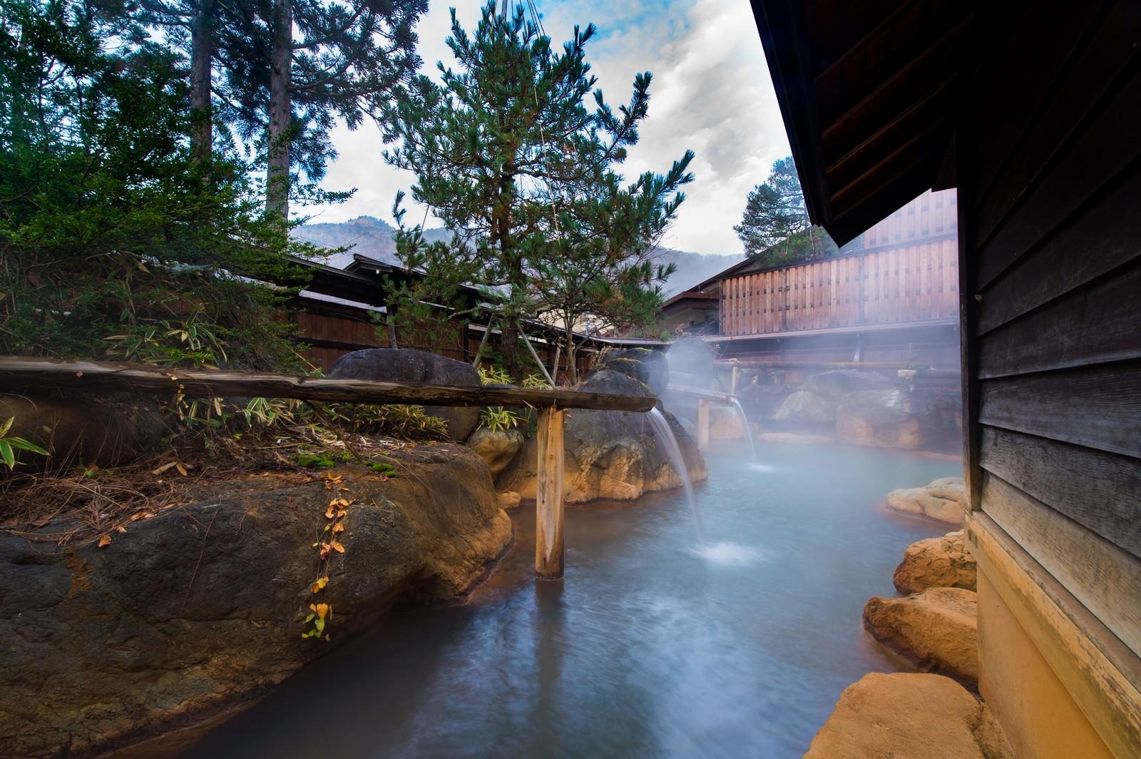 「内湯を囲む源泉かけ流しの大露天風呂」の写真