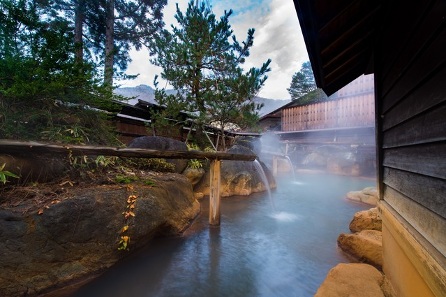 内湯を囲む源泉かけ流しの大露天風呂の写真