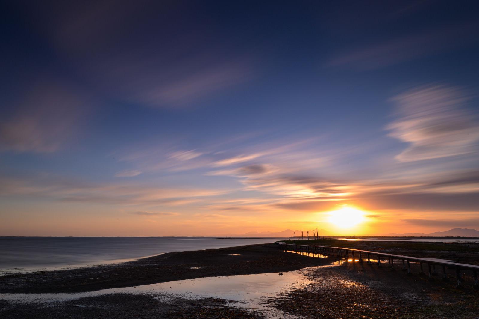 「野付半島の沈む夕日と桟橋」の写真