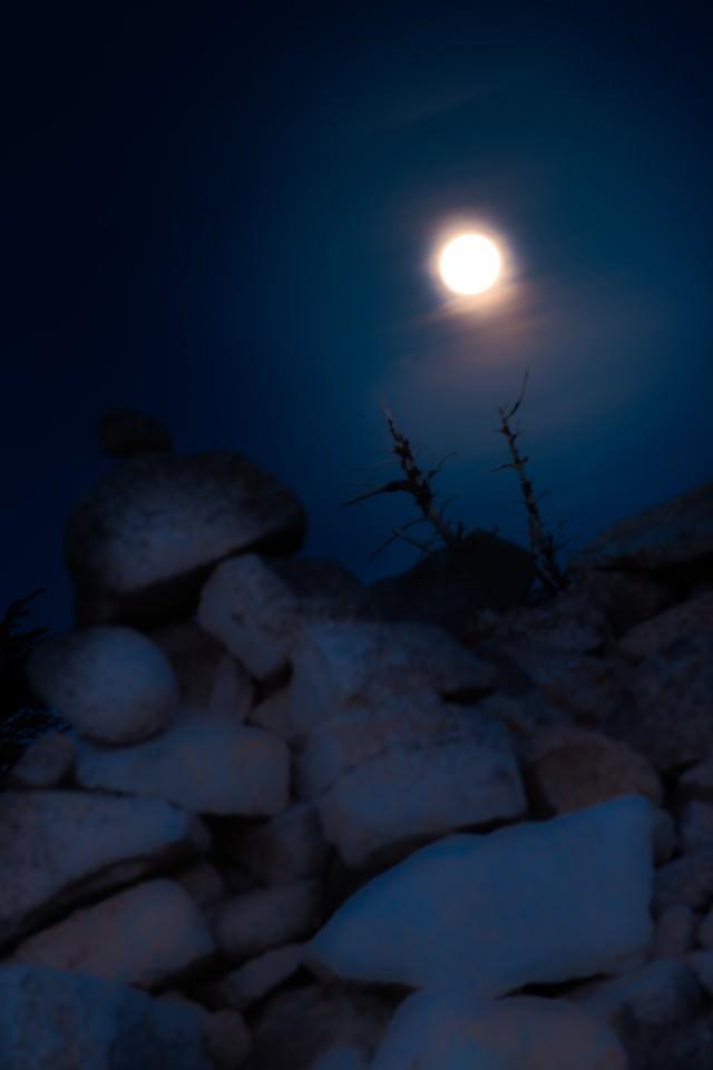 深夜の稜線のケルンと満月の写真
