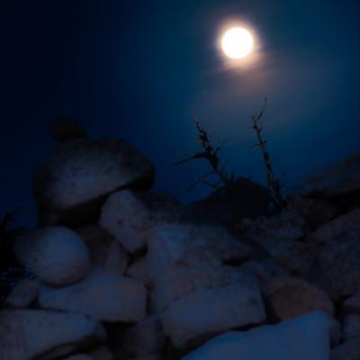「深夜の稜線のケルンと満月」の写真素材