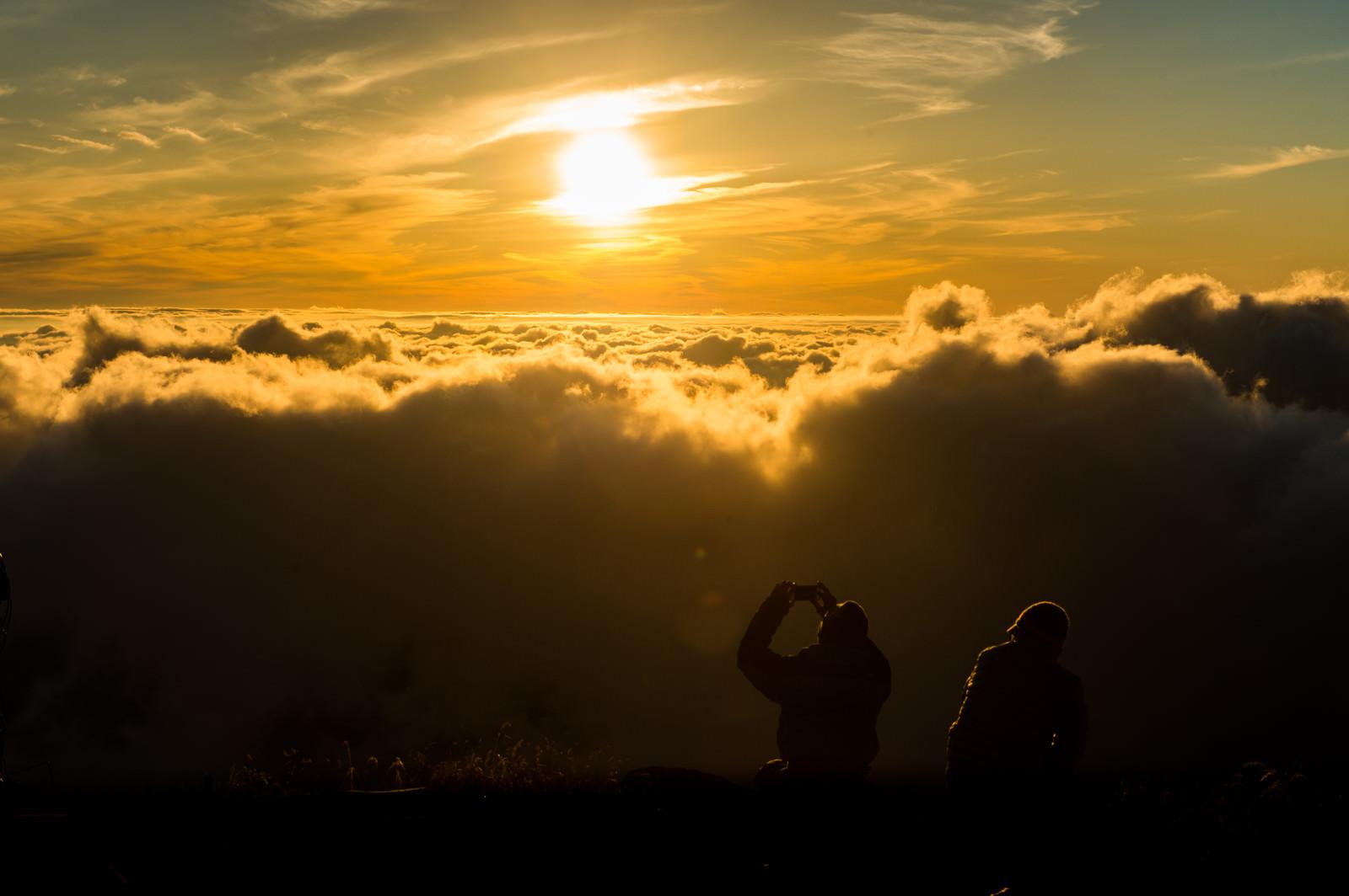 「夕暮れの雲海の絶景に感動するカップル」の写真