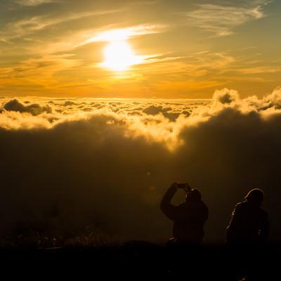 「夕暮れの雲海の絶景に感動するカップル」の写真素材