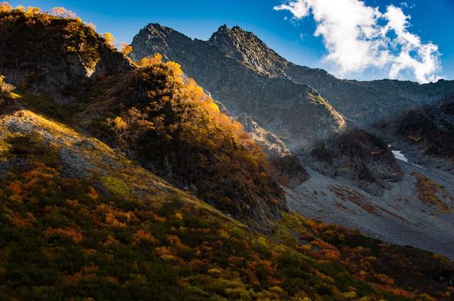 北アルプスの岩肌と涸沢カールの紅葉の写真