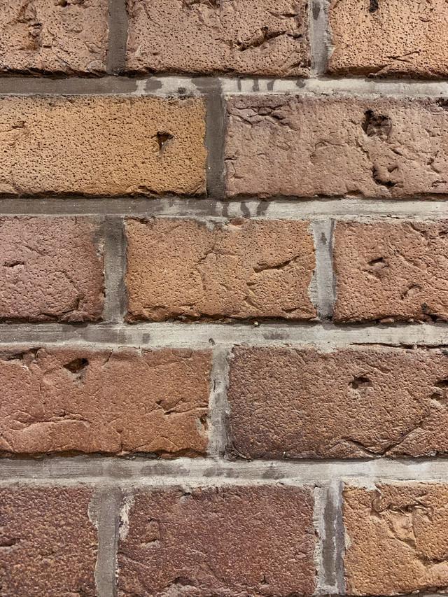 隙間をコンクリートで固められた煉瓦(テクスチャ)の写真