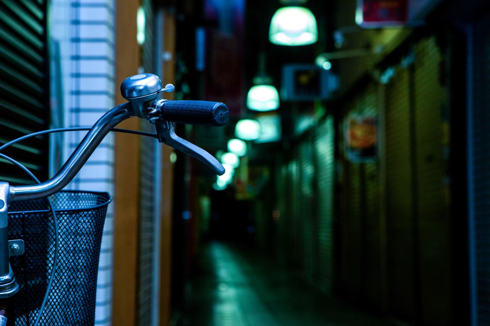 「自転車のハンドルと路地裏」の写真