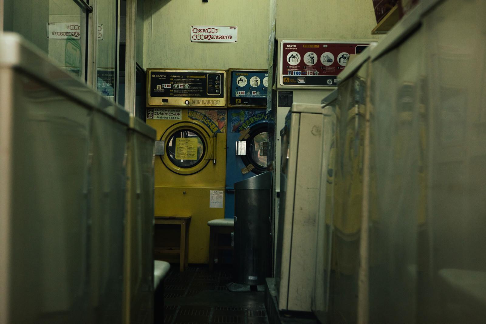「昭和レトロな洗濯機が並ぶコインランドリー」の写真