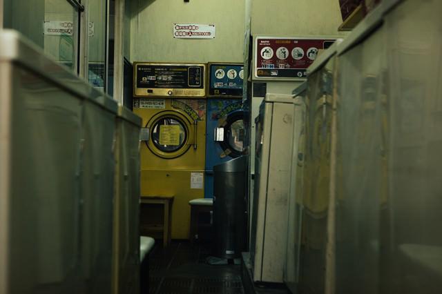 昭和レトロな洗濯機が並ぶコインランドリーの写真