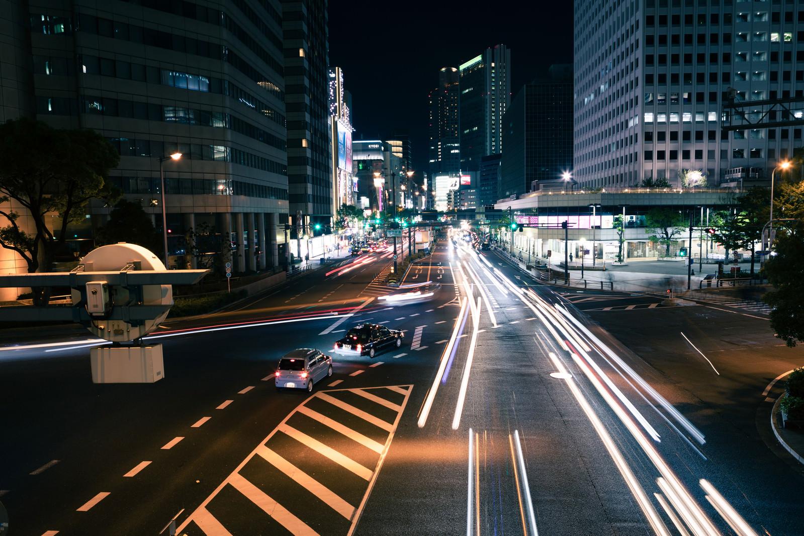 「夜の交差点を行き交う車」の写真