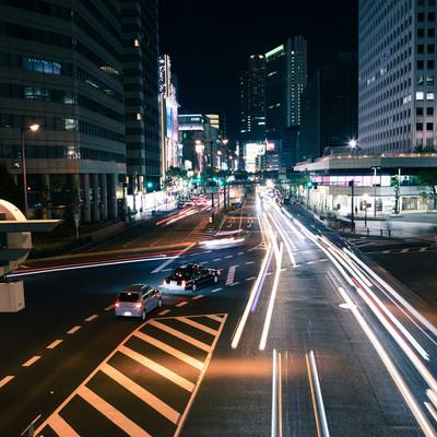 夜の交差点を行き交う車の写真