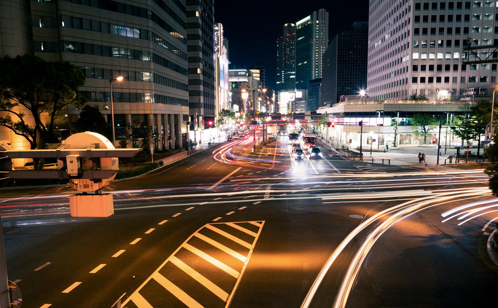 「夜の交差点を行き交う車の光跡」の写真