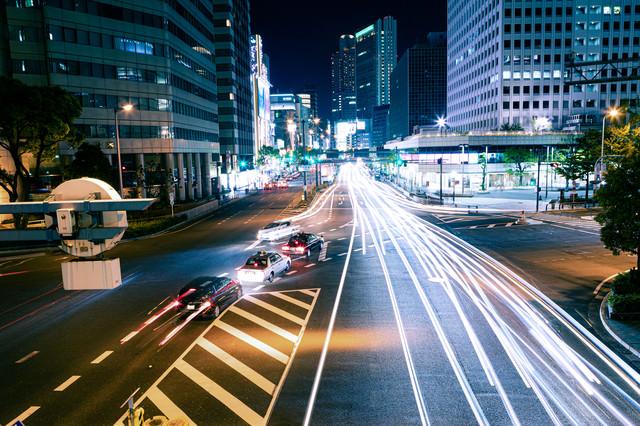 直進する車の光跡と右折レーンの車の写真