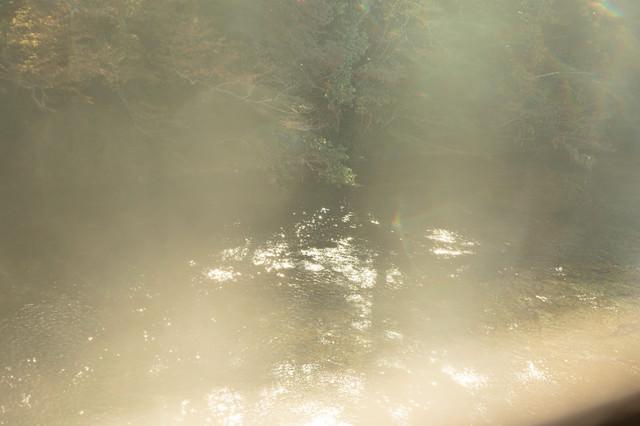 靄がかる湖面に反射する日の光の写真