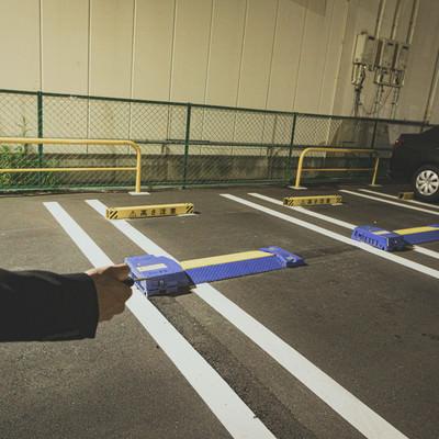 駐車場に停めた自動車を解錠するの写真