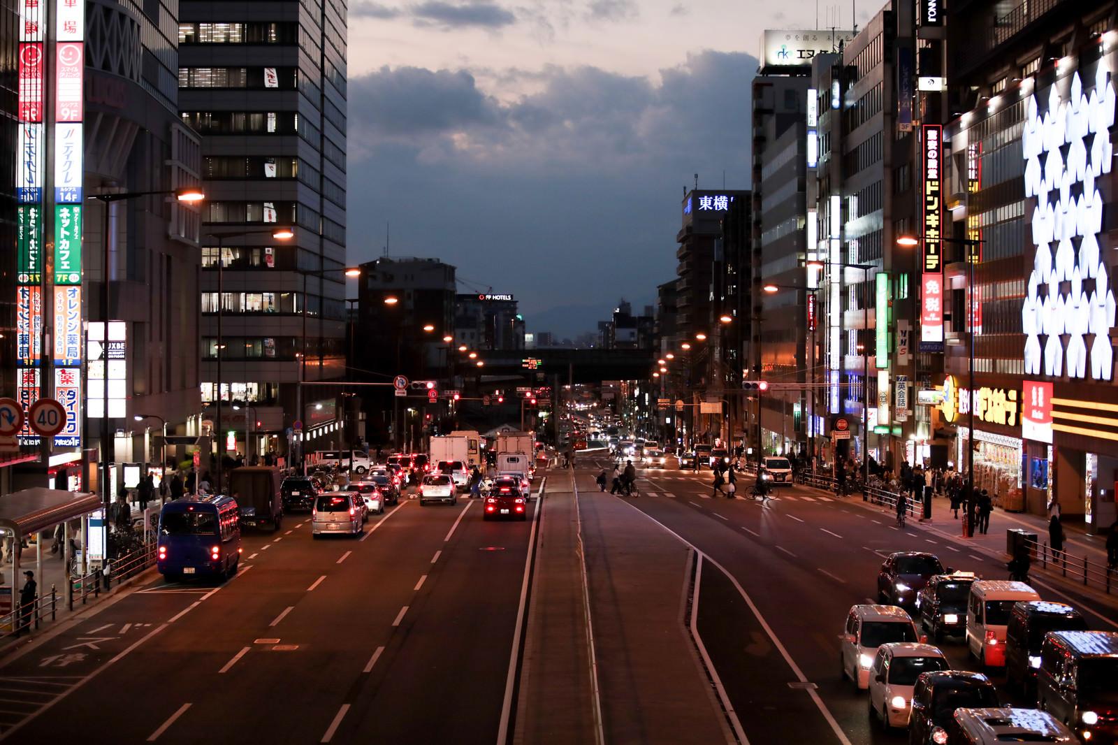 「赤信号で止まる車と街並み」の写真