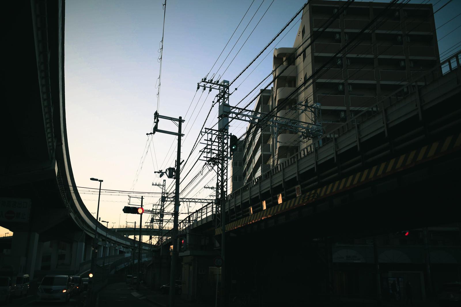 「青空に張り巡る電線と高架橋」の写真