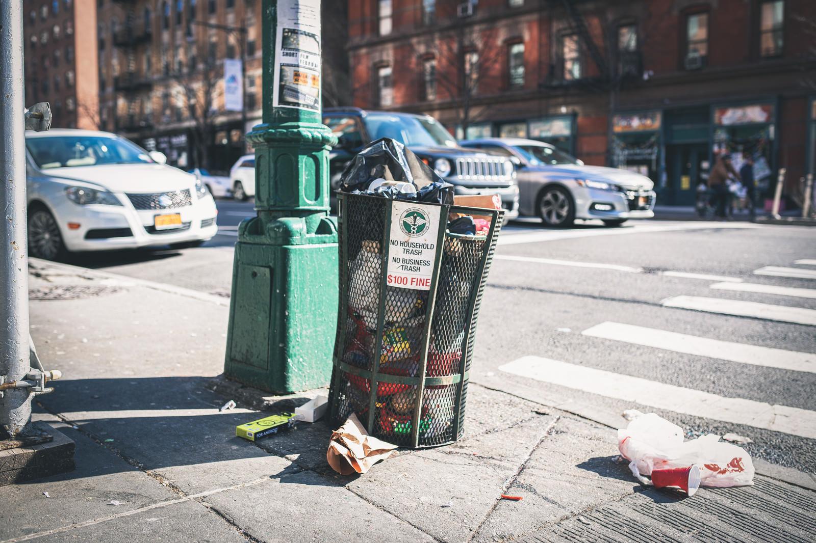 「ニューヨークの街角のゴミ箱と散乱するゴミ」の写真