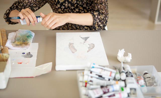キャンバスを前に絵具を用意する女性の写真