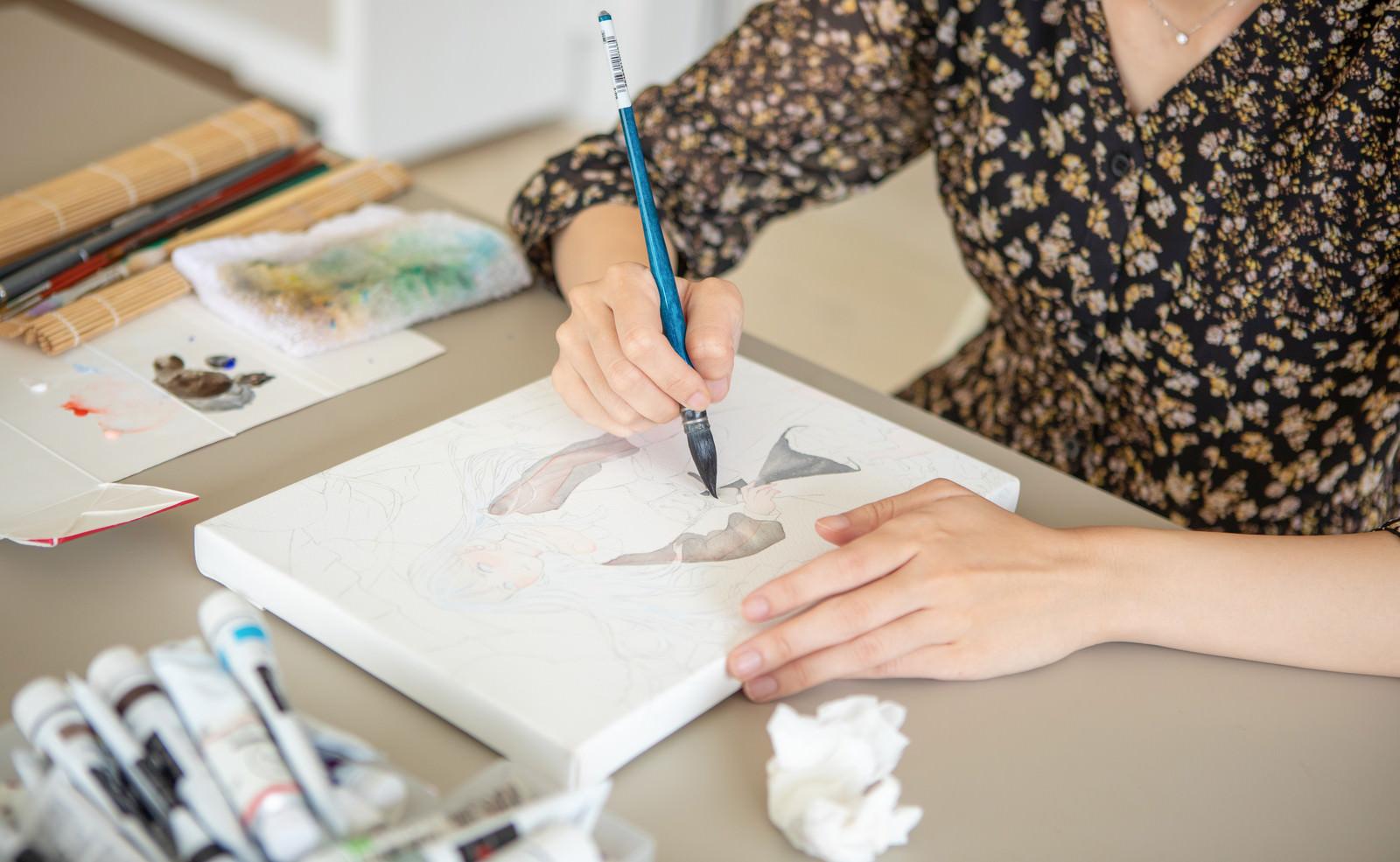 「キャンバスに書かれた絵柄に色付けをする女性」の写真