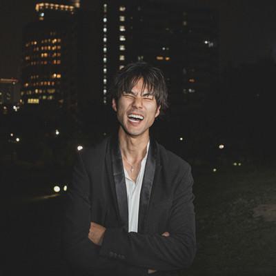 深夜の公園で大笑いする男性の写真