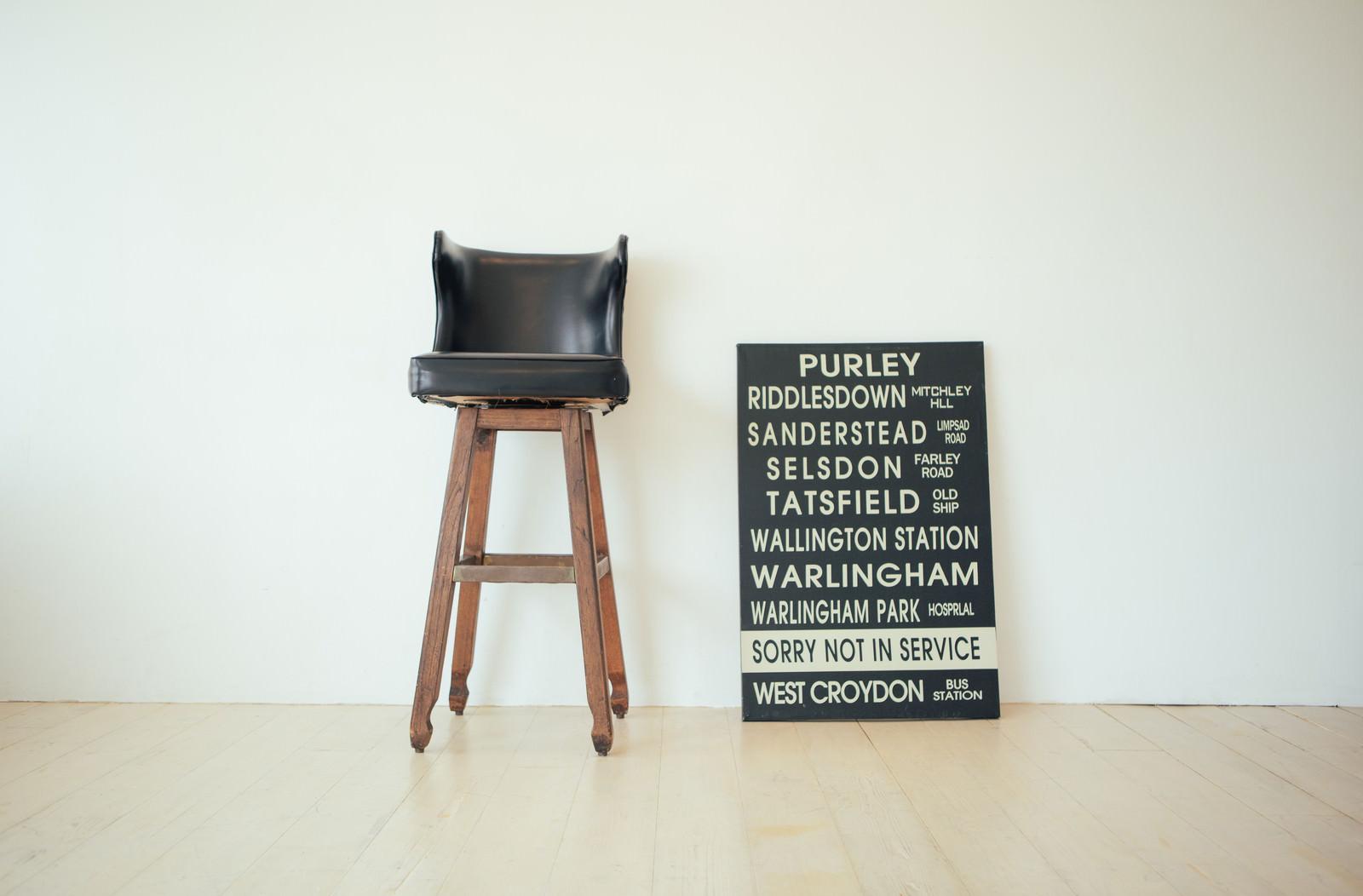 「無造作に置かれたバーチェアと看板」の写真