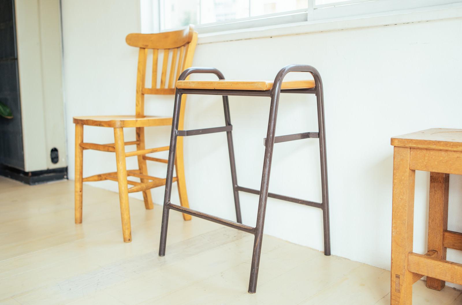 「木製の椅子の間に置かれたサイドテーブル」の写真