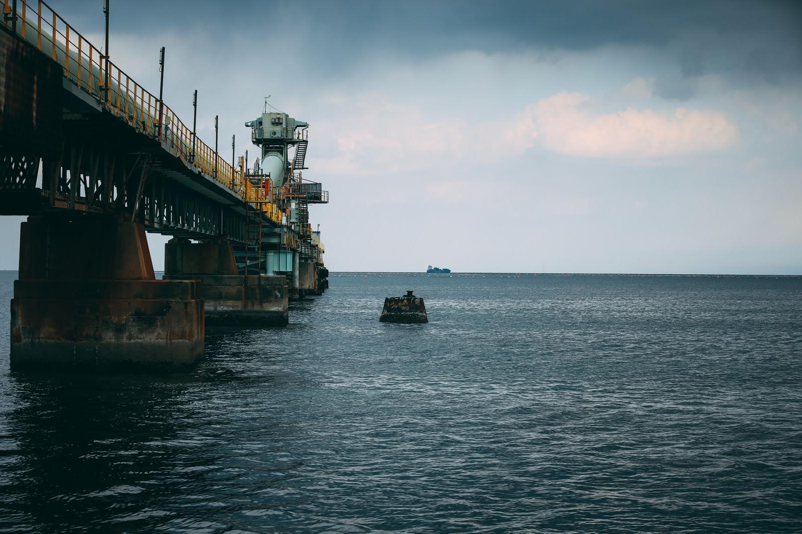 「海上工場の先に見る運搬船」の写真