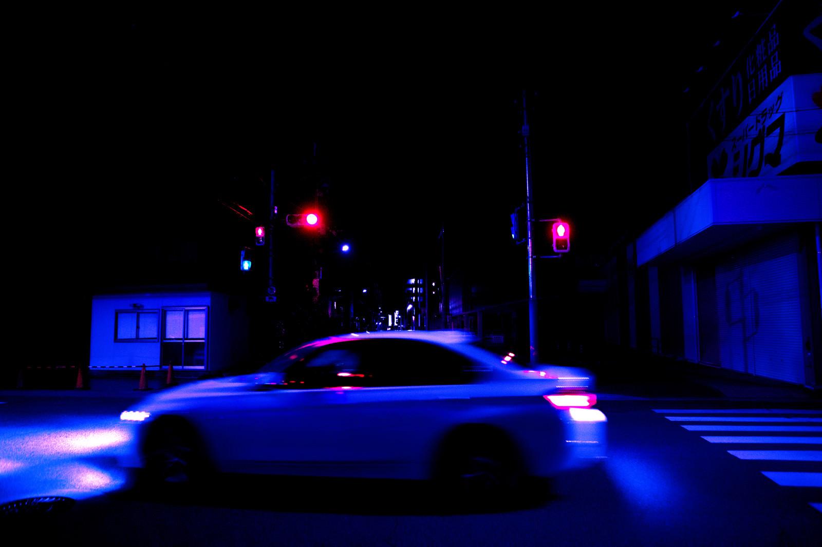 「深夜の交差点を走り去る自動車」の写真