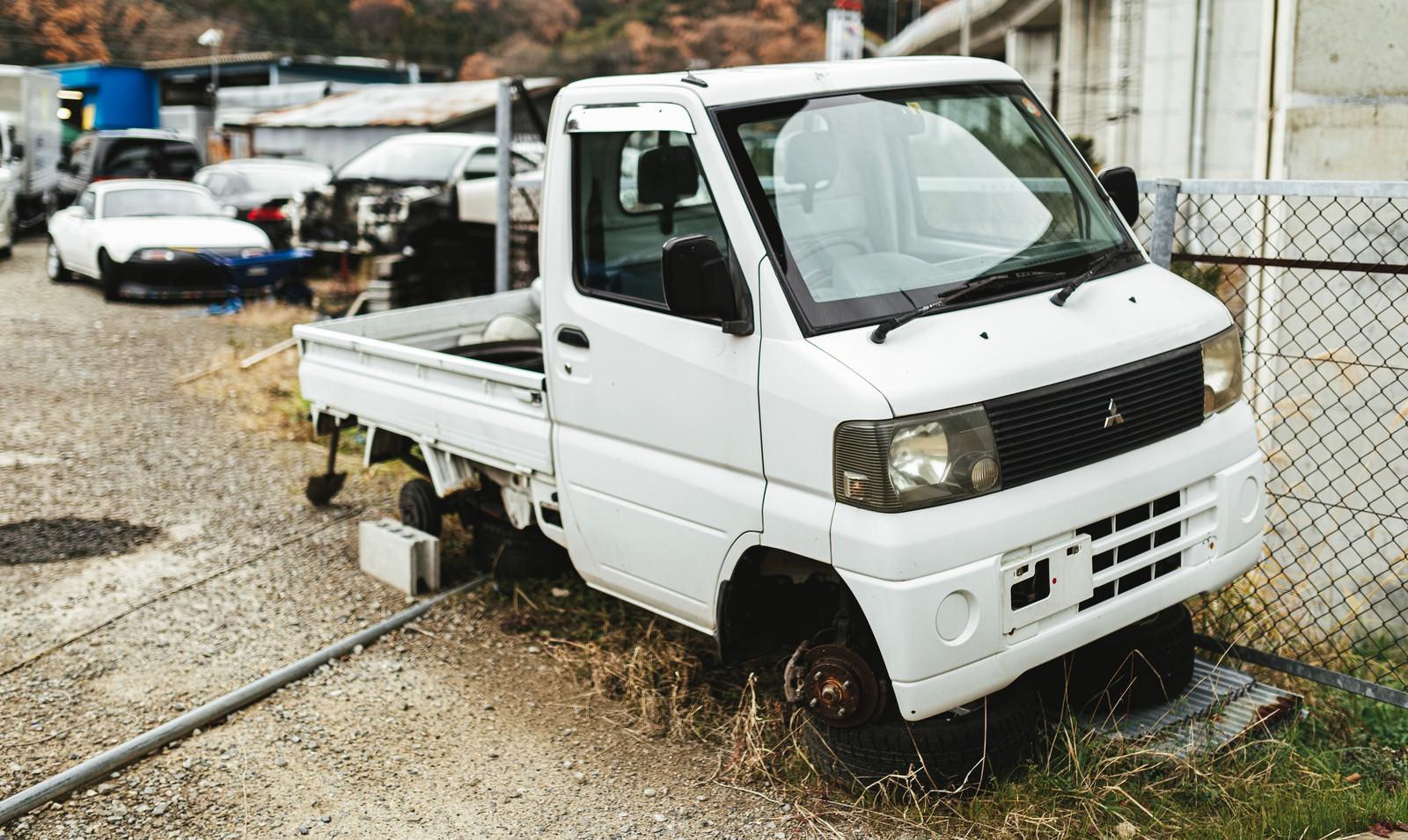 「タイヤが外れた軽トラック」の写真